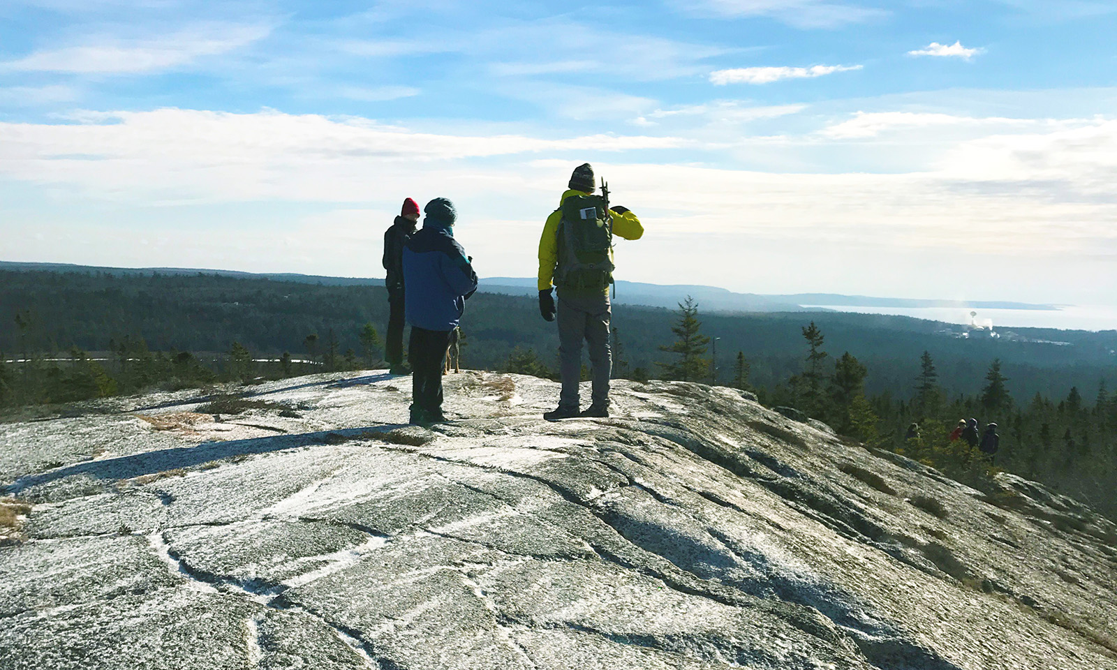 three people overlooking the forest from a high rock outcropping