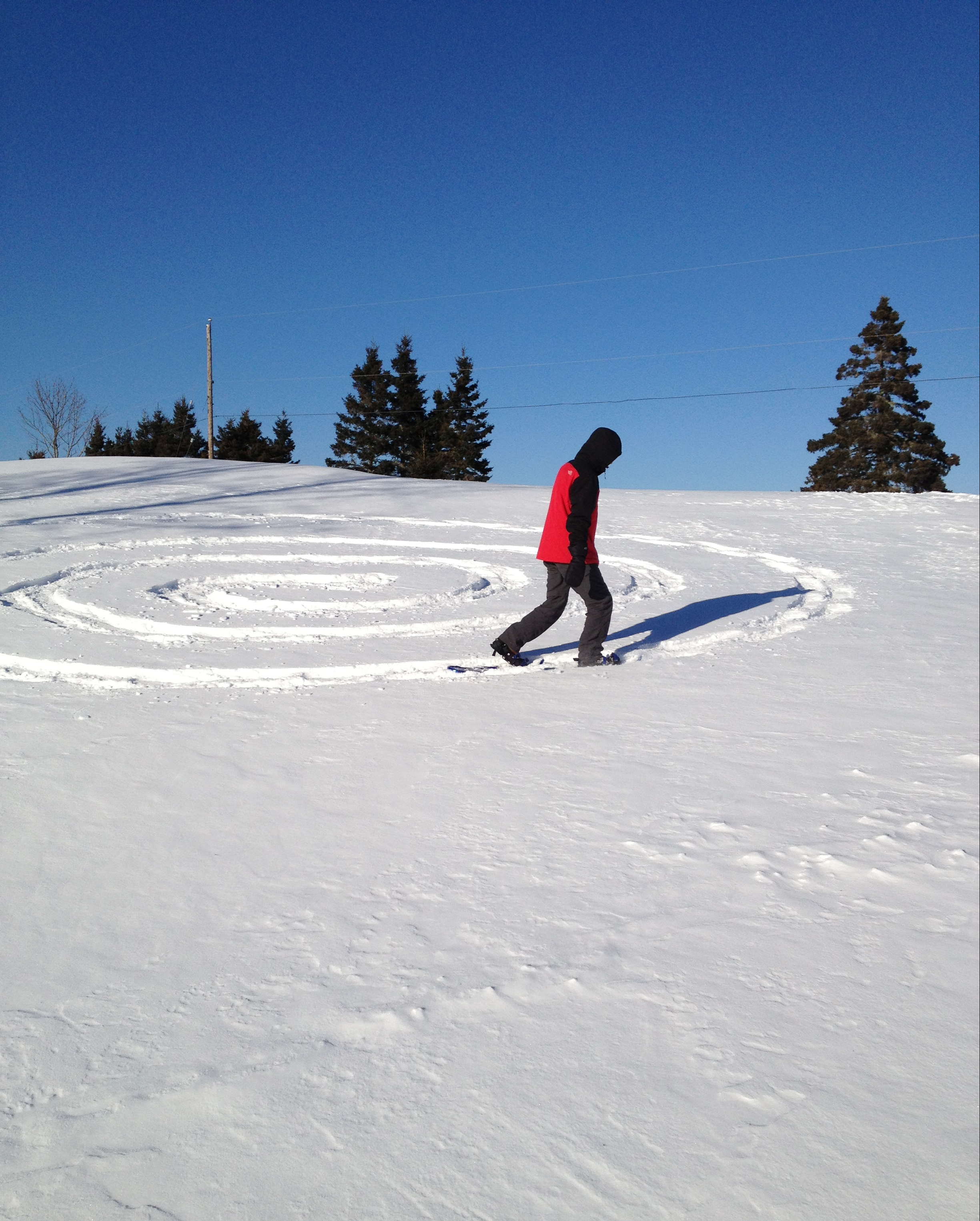 A person walking on a hill in circles with their snowshoes