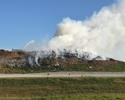 Kaizer Meadow landfill face on fire while Hantsport Fire Department aerial truck fights smoldering blaze.