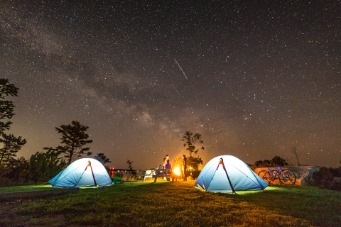 two illuminated tents at night with blazing fire and a backdrop of a star-filled night sky with a falling star
